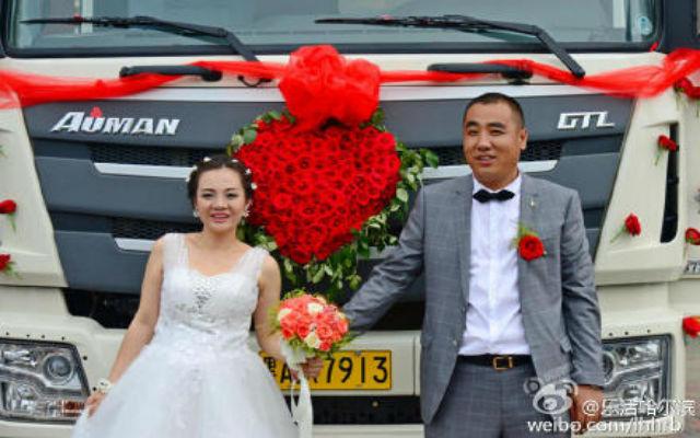 Cặp đôi tân lang, tân nương chụp ảnh bên chiếc xe tải đón dâu.