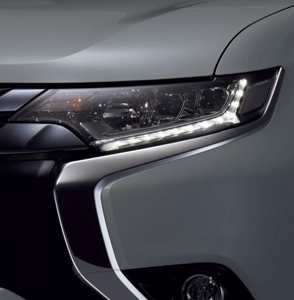 Một phần đầu xe của Mitsubishi Outlander PHEV 2016 với viền lưới tản nhiệt mạ crôm và dải đèn LED chiếu sáng ban ngày.