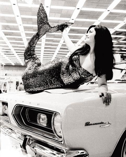 Một người mẫu đóng vai nàng tiên cá và nằm trên chiếc xe Plymouth Barracuda 1964 tại triển lãm Detroit 1963. Người mẫu xe bắt đầu trở thành xu hướng từ khoảng giữa thập niên '50 của thế kỷ trước. Tuy nhiên, phải đến giữa thập niên '80, người mẫu xe mới được yêu cầu có kiến thức về sản phẩm.