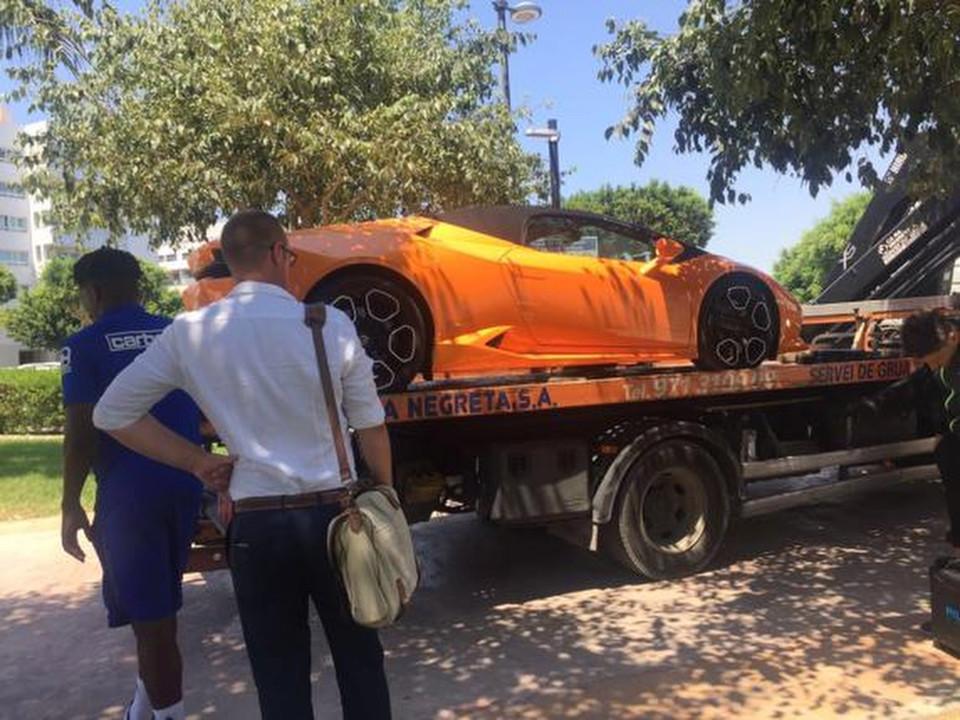 Chiếc Lamborghii Huracan màu cam bị đưa về đồn trên xe cứu hộ.