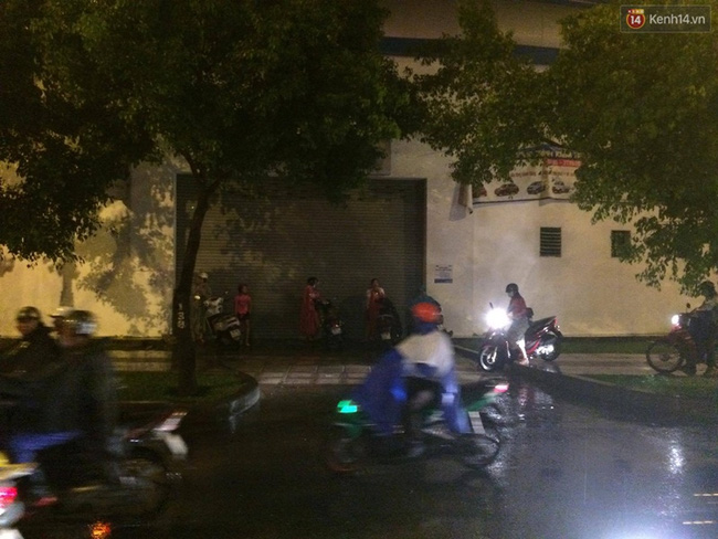 Nhiều người phải lên vỉa hè chờ hết kẹt xe và mưa rồi mới đi tiếp. Ảnh: Tứ Quý