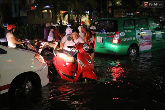 Người đàn ông tình nguyện dắt xe lên vỉa hè cho những người có phương tiện chết máy khi đang lưu thông. Ảnh: Quỳnh Trân