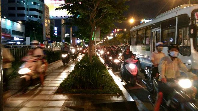 Gần 18h40, đường Trường Sơn hướng sân bay Tân Sơn Nhất đi vòng xoay Lăng Cha Cả ùn tắc, di chuyển khó khăn. Đoạn vỉa hè tại đây trở thành nơi để người tham gia giao thông chen lấn thoát kẹt xe.