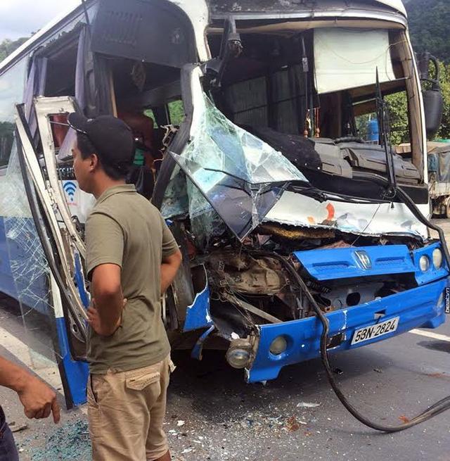 Tài xế xe tải cùng nhiều người dân phải dùng dây xích để kéo đỡ phần đầu bị móp nặng để giải cứu chủ xe khách đang đau đớn vì bị kẹt chân. Ảnh: CAND.