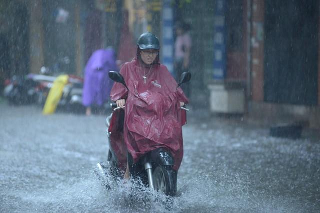 Người đi xe máy khổ sở vì mưa lớn và đường ngập. Ảnh: Đại Nguyễn Thế