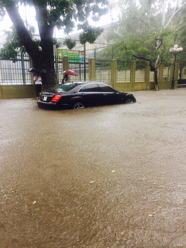 Nước ngập quá nửa bánh ô tô tại khu vực Cầu Giấy. Chủ xe đã phải gọi xe cứu hộ đến.
