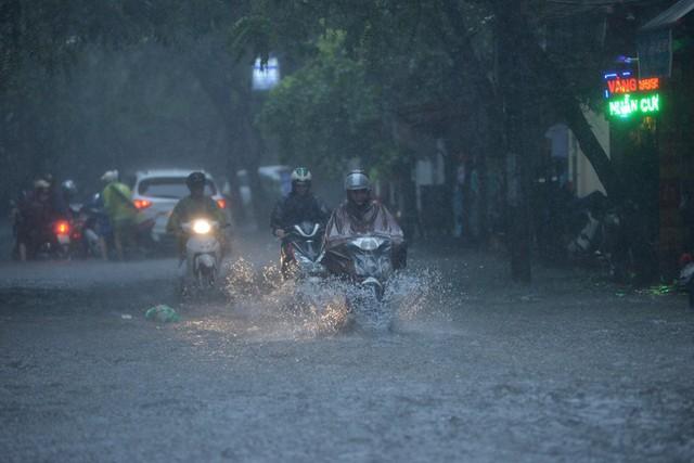 Người dân thủ đô cố gắng di chuyển trên đường ngập tại khu vực Ngã Tư Sở. Ảnh: Đại Nguyễn Thế