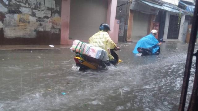 Nhiều người đã phải xuống xe máy dắt bộ vì nước ngập sâu, quá cả ống xả.