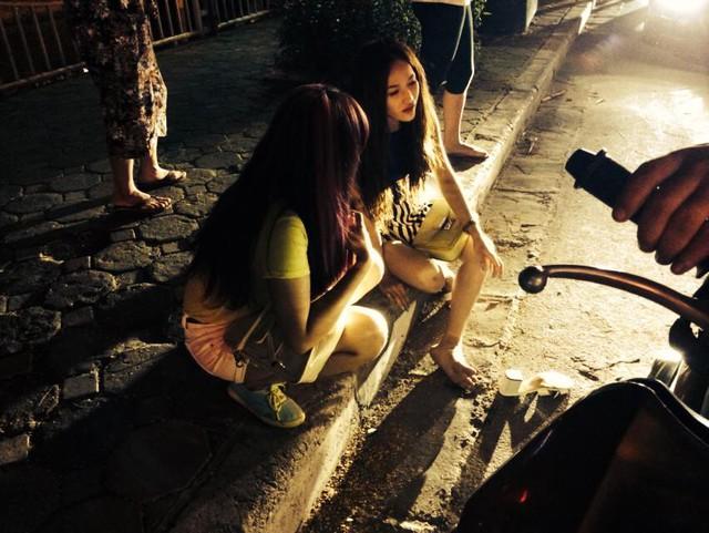 Hai cô gái ngồi trên chiếc xe máy bị tai nạn.