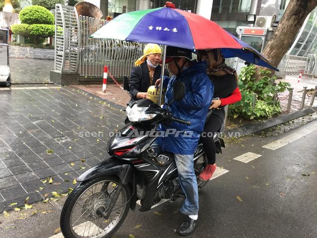 Một sáng chế lắp thêm ô vào xe để che mưa che nắng cho cả người lái xe và người ngồi sau.