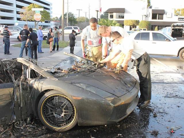 Lực lượng chức năng kiểm tra chiếc siêu xe Lamborghini Gallardo sau khi dập lửa.