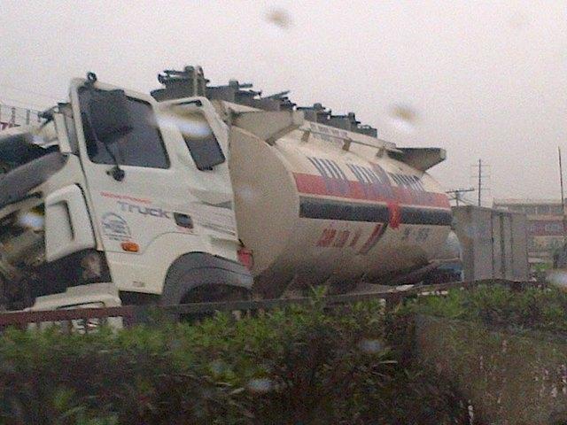 Xe bồn chở xăng bị ngoặt đầu sang bên sau cú va chạm với xe container.