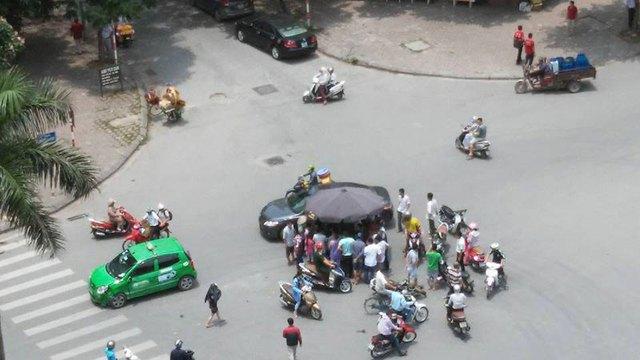 Một người bán hàng mang ô ra che cho nạn nhân giữa trưa nắng. Ảnh: Lê Tấn/Otofun