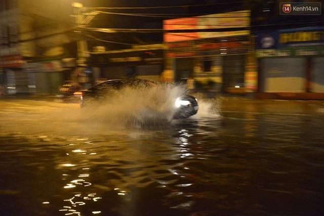 Một chiếc xe ô tô dũng mãnh xé nước để vượt qua chỗ ngập. Tuy nhiên, việc này có thể tạo ra các cơn sóng lớn xô vào các phương tiện hai bánh khác hoặc làm nước ngập dềnh vào các nhà dân xung quanh. Ảnh: Kenh14.vn
