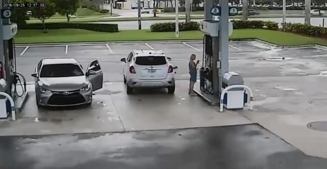 Nữ tài xế đứng quay lưng lại và mải mê đổ xăng. Ảnh cắt từ video