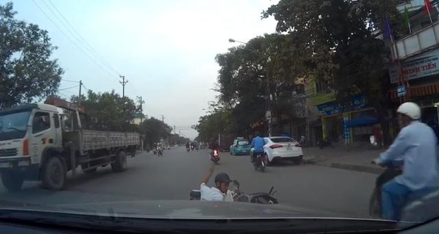 Cả người và xe ngã trước đầu ô tô. Ảnh cắt từ video