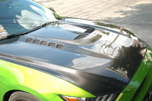Ngoài bộ áo xanh chuối cá tính, người chơi xe còn độ thêm các chi tiết ở ngoại thất cho chiếc Ford Mustang này như nắp capô, cánh lướt gió cỡ lớn phía trước và cản va sau bằng chất liệu sợi carbon.