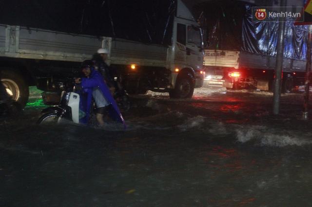 Tái diễn cảnh vất vả dắt xe chết máy qua những đoạn ngập sâu ở Sài Gòn.