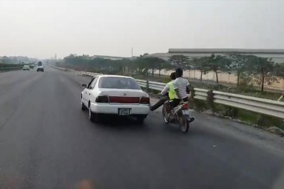 Bàn chân vàng trong làng cứu hộ: Nam thanh niên đi xe máy dùng chân không đẩy ô tô chạy băng băng trên cao tốc - Ảnh 2.