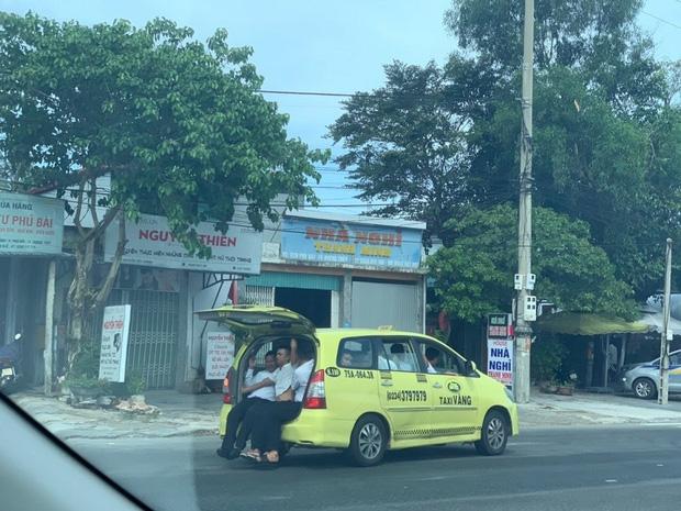 """Taxi 7 chỗ """"nhồi"""" 11 người, 3 người ngồi cốp xe như làm xiếc - Ảnh 1."""