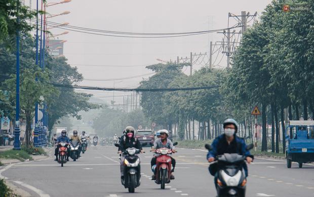 Sài Gòn bị bao phủ một màu trắng đục từ sáng đến trưa, người dân cay mắt khi đi ngoài trời - Ảnh 12.