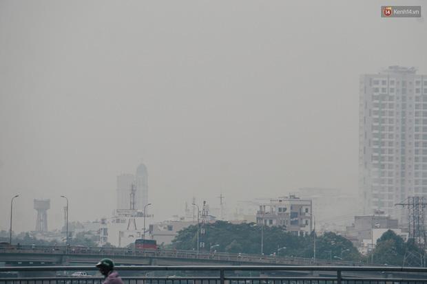Sài Gòn bị bao phủ một màu trắng đục từ sáng đến trưa, người dân cay mắt khi đi ngoài trời - Ảnh 9.