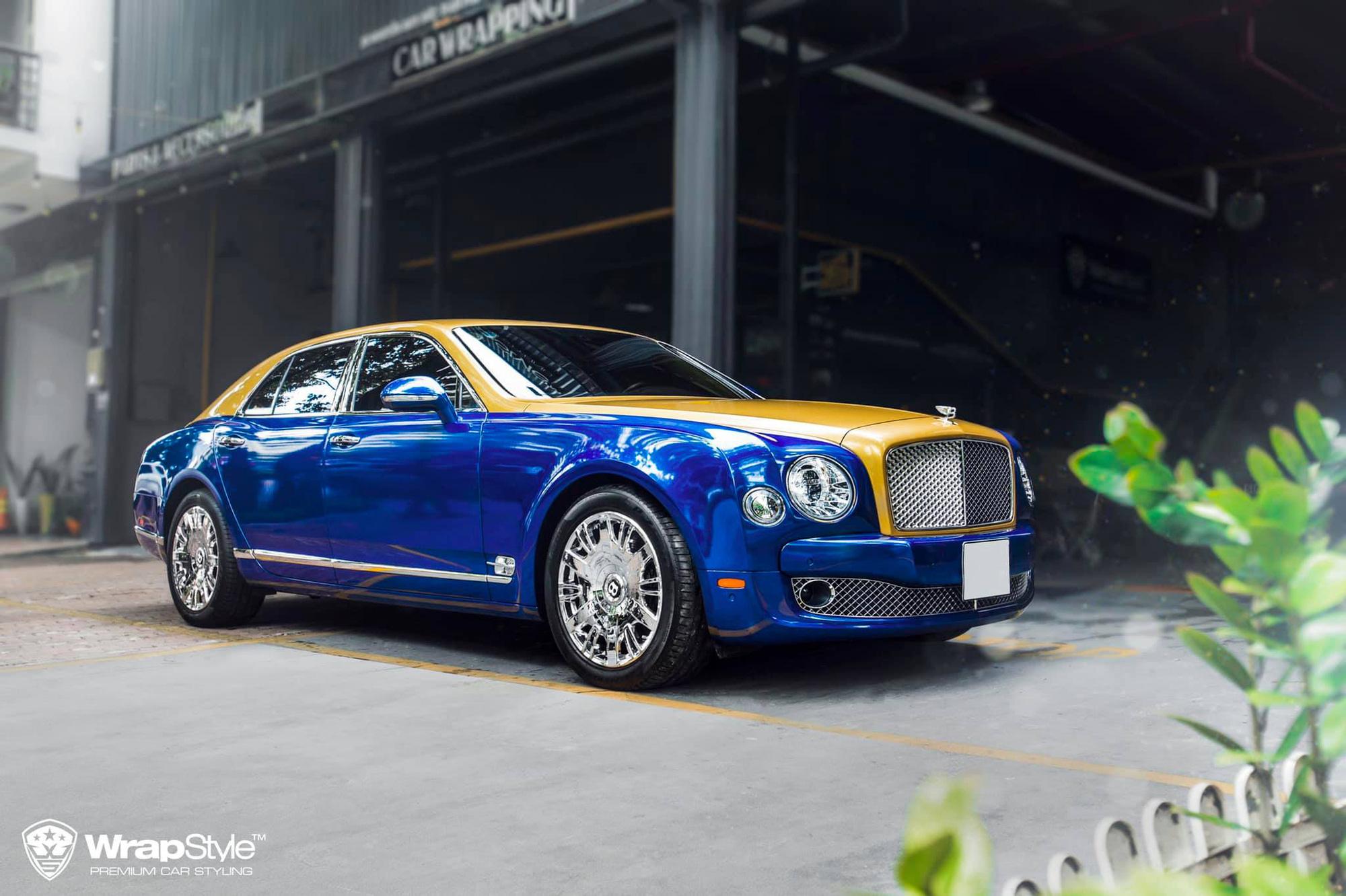 Hình ảnh chiếc Bentley Mulsanne khác lạ khiến không ít người tò mò. Điểm nổi bật là lớp decal hai tông màu độc đáo. Cụ thể, phần nóc xe được dán decal màu vàng đồng, trong khi phần thân được dán màu xanh dương lạ mắt.
