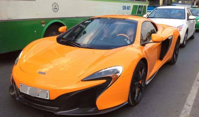 Minh Nhựa ngồi sau vô lăng siêu xe McLaren 650S Spider màu cam nổi bật.