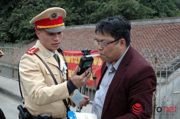 Lái xe Lê Hữu Cảnh thổi máy đo nồng độ cồn trong khí thở.