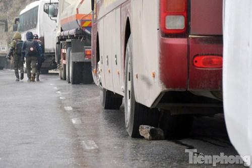 Đường trơn và dốc khiến các tài xế phải dùng đá chèn vào bánh xe.