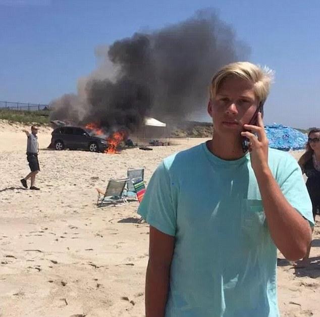 Chàng trai trẻ với mái tóc vàng óng dường như không hề biết chuyện gì đang xảy ra sau lưng mình. Chàng trai mải mê nói chuyện điện thoại trong khi một chiếc ô tô đang cháy đùng đùng phía sau.