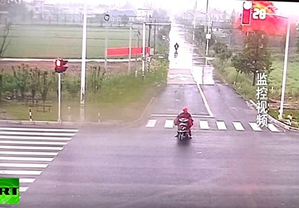 Người đàn ông mặc áo mưa đang đỗ xe chờ sang đường. Ảnh cắt từ video