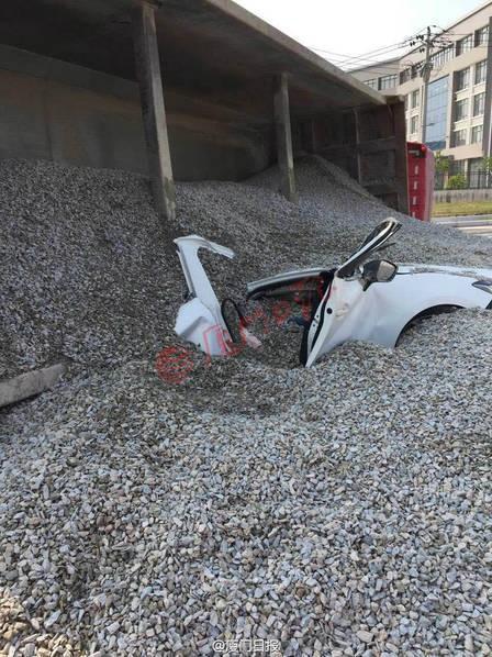 Chiếc ô tô con bị vùi trong sỏi đá.