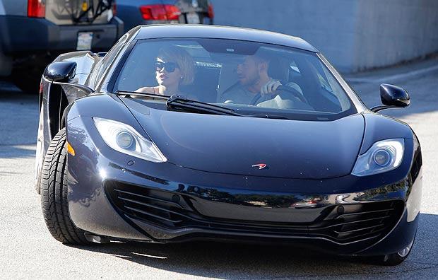 Calvin Harris cầm lái chiếc siêu xe McLaren 12C Coupe màu đen, chở bạn gái cũ Rita Ora.