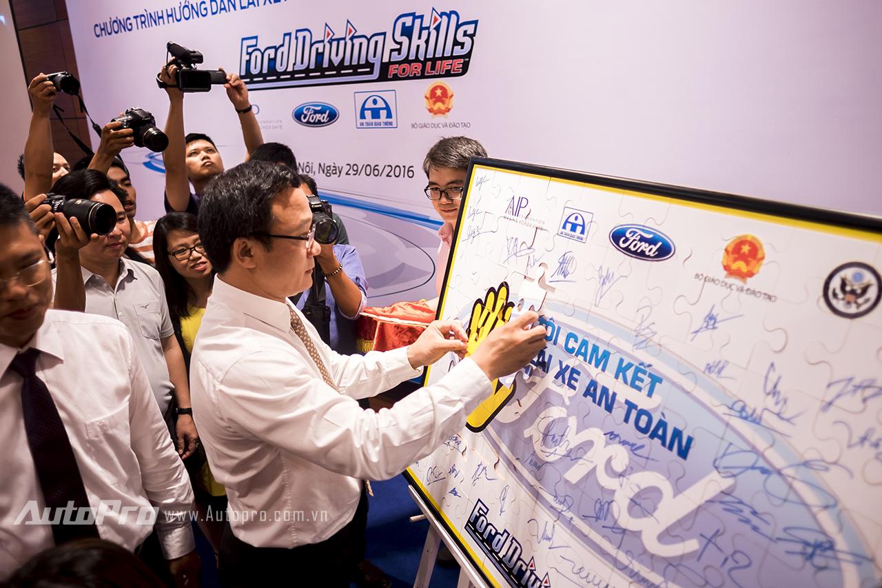 Ông Khuất Việt Hùng ký tên cam kết lái xe an toàn tại buổi họp báo.