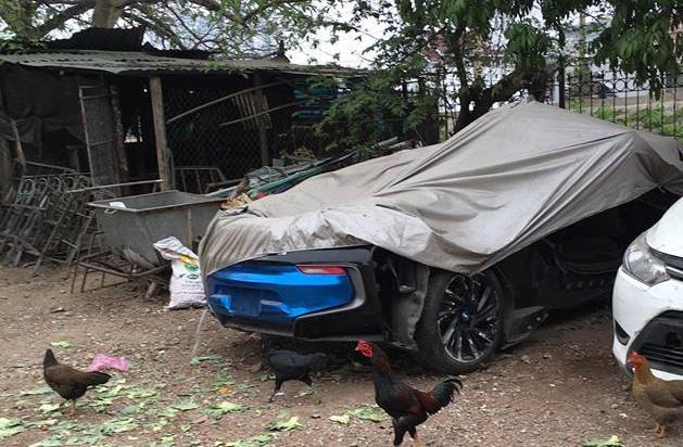 BMW i8 phủ bạt trong khuôn viên chuồng gà. Ảnh: Facebook.