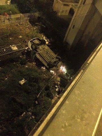 Chiếc taxi nằm ngửa bụng khi rơi từ cầu xuống mặt đất.