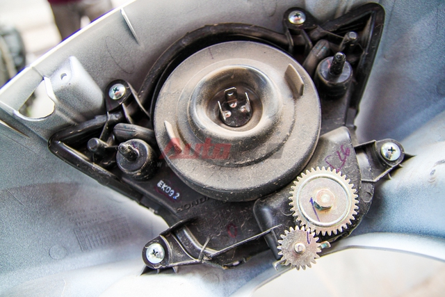 Chi tiết mặt sau của cụm đèn chiếu sáng với phần bánh răng chỉnh độ nghiêng (xa) của đèn. Hệ thống đèn trên Honda SH 2015 được sản xuất bởi Stanley.