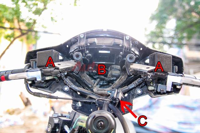 Chi tiết phần đầu xe. A: phanh dầu, B: công tơ mét điện tử, C: giắc đèn chiếu sáng.