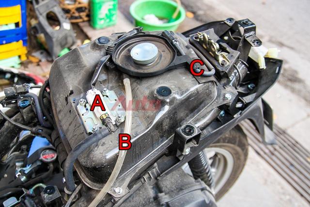 Chi tiết phần bình xăng. A: bơm xăng, B: ống dẫn xăng tràn, C: ống thoát hơi bình xăng. Cụm IC kiêm sạc của xe nằm phía dưới bình xăng.