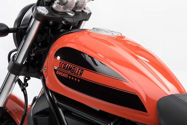 """Bên cạnh đó, Ducati Scrambler Sixty2 còn có một số điểm khác biệt về thiết kế so với phiên bản 800 phân khối. Có thể nhận thấy điều đó qua dòng chữ """"Scrambler"""" đậm chất cổ điển trên bình xăng bằng thép."""