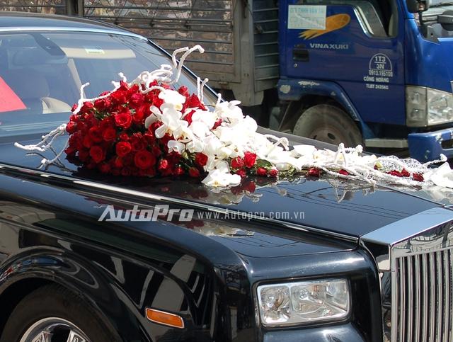 Chùm hoa hồng màu đỏ và lan hồ điệp màu trắng nổi bật trên nắp capô.