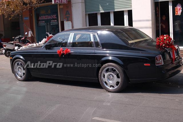 Chiếc Rolls-Royce Phantom sở hữu bộ vest đen lịch lãm, đối lập với dàn hoa cưới đỏ rực trên nắp capô và đuôi xe