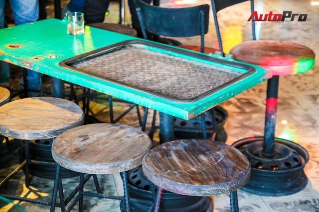 Mặt bàn làm bằng cánh cửa xe ô tô. Chân ghế là từ những chiếc vành cũ.