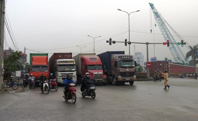 Xe container xếp hàng 4, sang cả làn đường xe máy khiến nhiều người phải len lỏi vượt qua các hàng xe.
