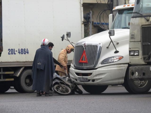 Tai nạn xảy ra khi xe máy và xe container đều cố giành đường.