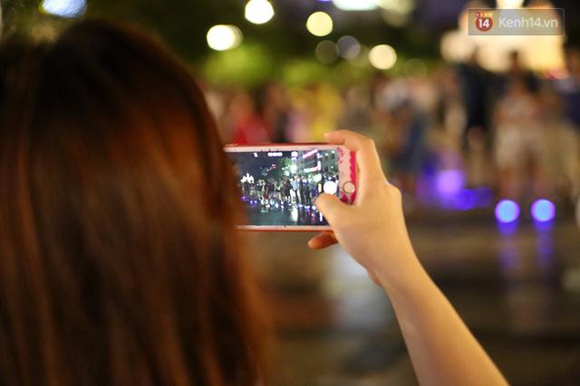 Người dân thích thú ghi lại đoàn người biểu diễn trên phố.