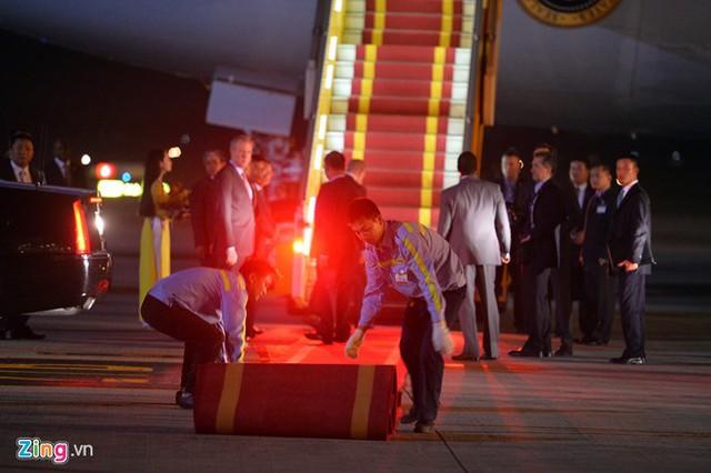 Nhân viên mặt đất cảng hàng không trải thảm từ chân cầu thang phục vụ.