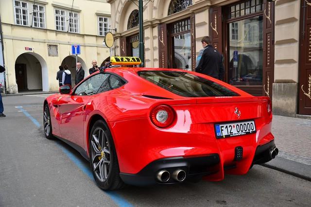 Siêu xe Ferrari F12 Berlinetta màu đỏ rực gắn mào taxi trên nóc.