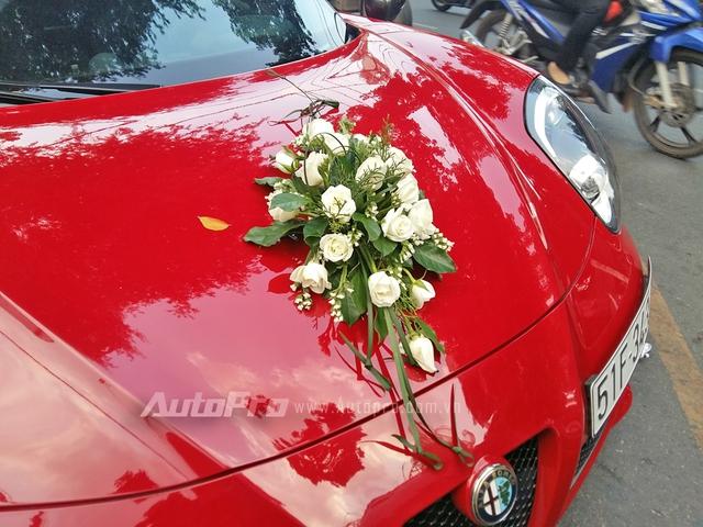 Những chiếc xe đưa dâu đều được trang trí đơn giản với hoa hồng trắng được kết trước đầu, bên hông và đuôi xe. Trong ảnh là chiếc Alfa Romeo 4C Launch Edition.